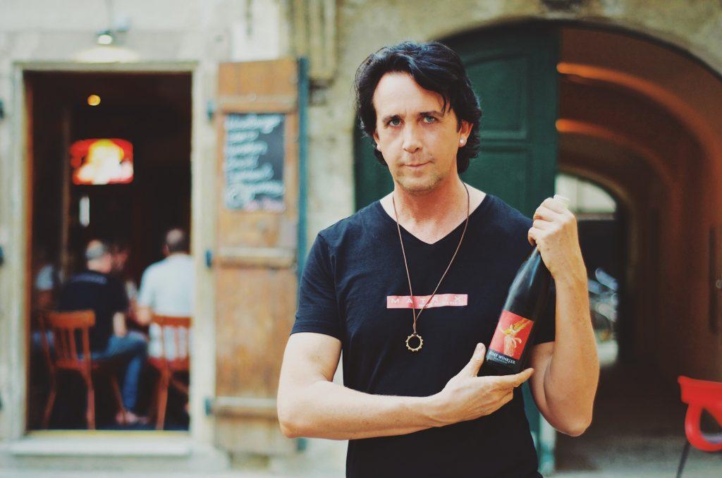 """Josef Winkler als Winzer: mit seinem eigenen """"Hauswein"""" in Händen vor seinem Shop im 1. Bezirk /Foto: Markus Neubauer"""